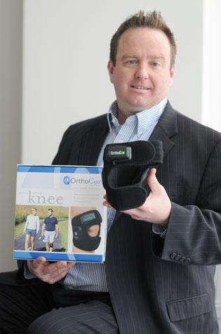 OrthoCor Medical CEO John Dinusson holds up his company's product, a pain-fighting knee wrap. Nancy Kuehn | Minneapolis/St. Paul Business Journal